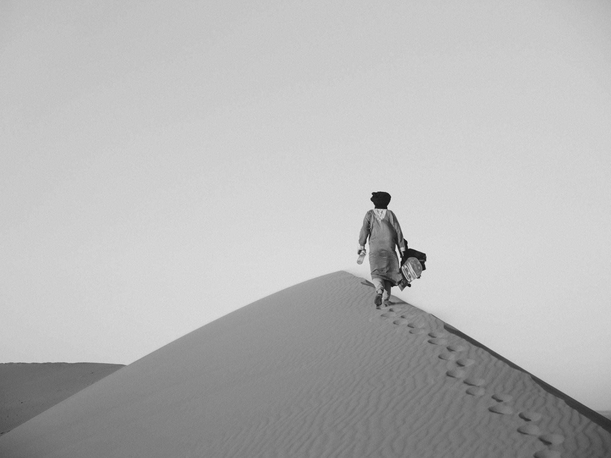 Moroccan Desert Sandboarding Instructor Walking along the Sand Dunes
