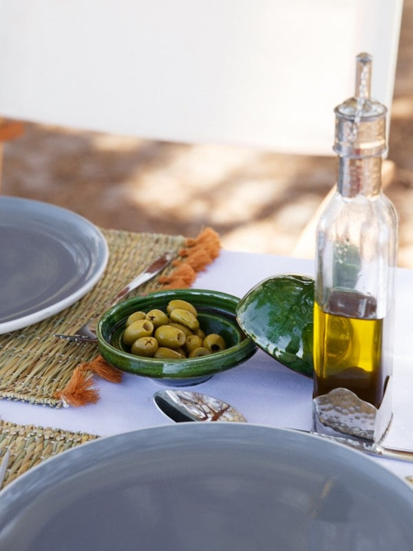 Fresh Olives and Olive Oil Condiments on Dining Table at Desert Camp
