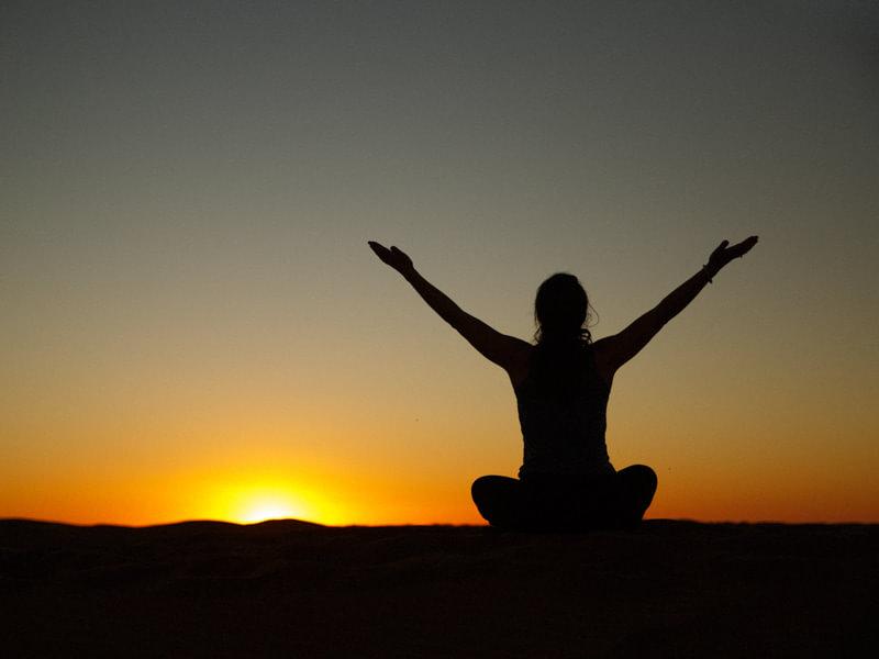 Silhouette of Woman in Yoga Lotus Meditation at Sunrise in Sahara Desert