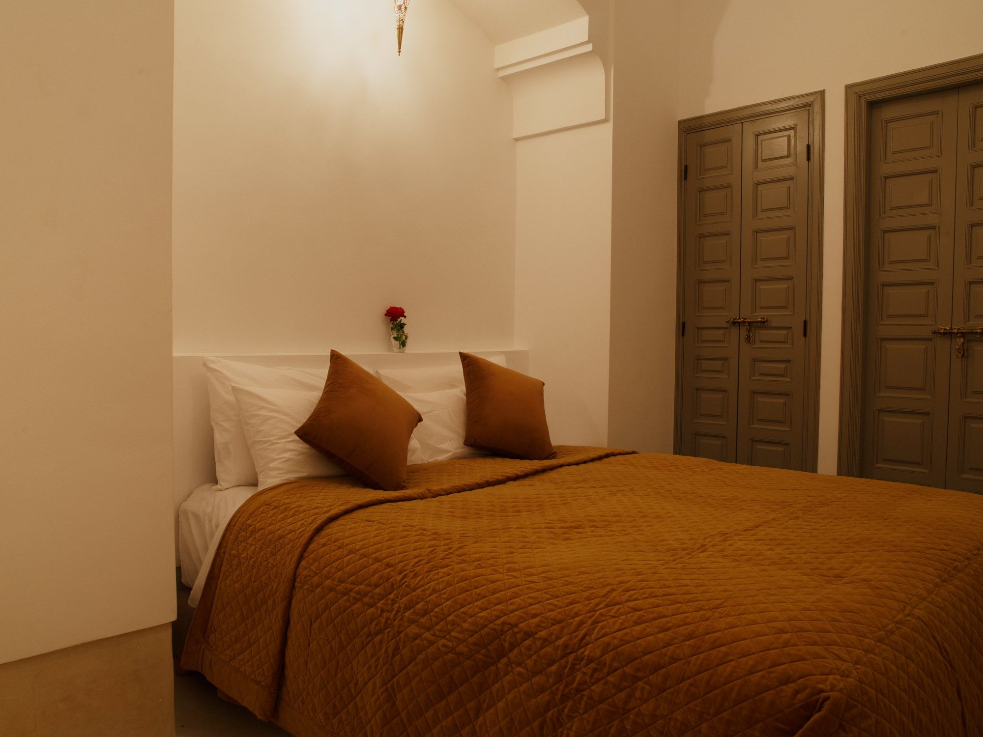 Riad Hotel bedroom, double bed and pillows, brown quilted top blanket, fitted wardrobes, Morocco