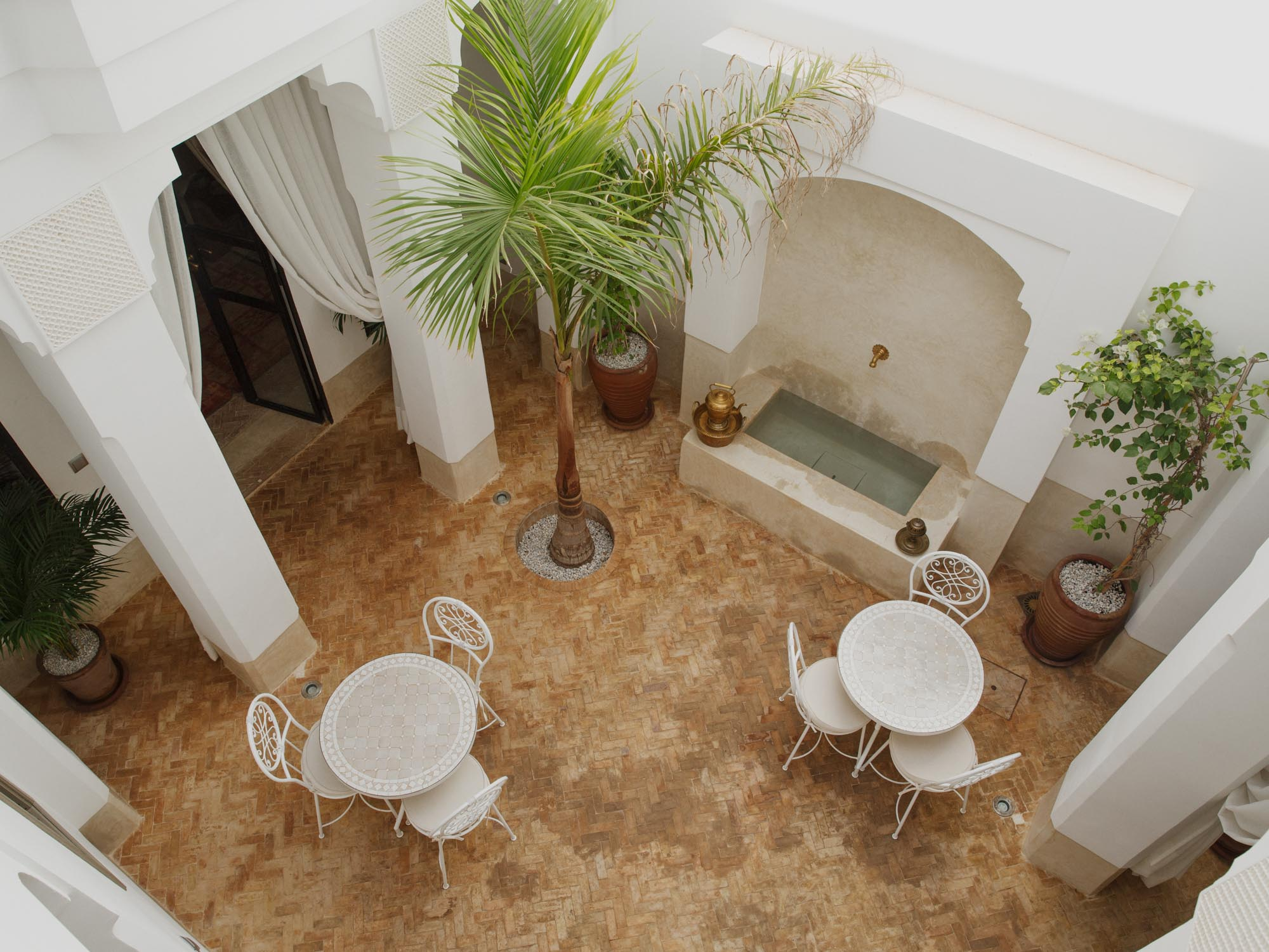 View of Hotel Room Patio from upper Balcony showing tables, chairs, plants and water fountain.