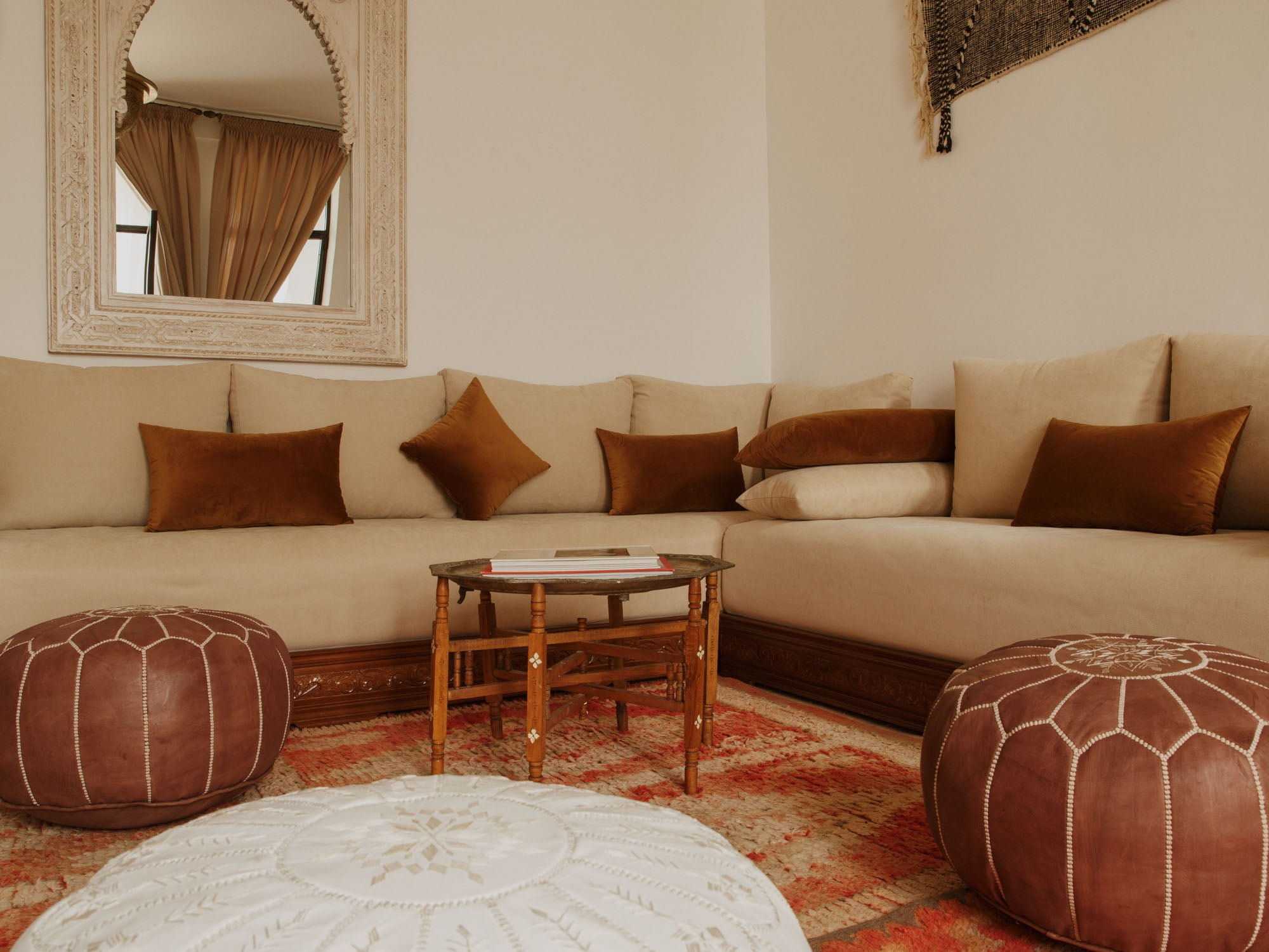 Hotel Room with decorative Window Surround, Couch with Cushions, Moroccan Pouf's, Red and White Rug and Occasional table
