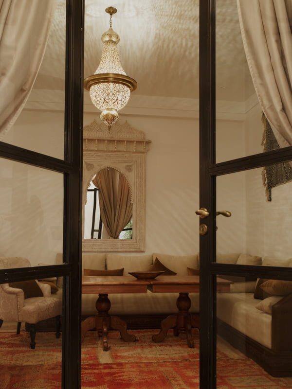 hotel room, ornate chandelier, curtains, couches and dining tables