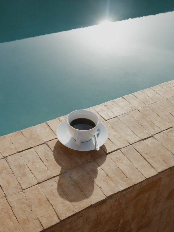 Cup of Tea sitting on wall, next to Swimming Pool