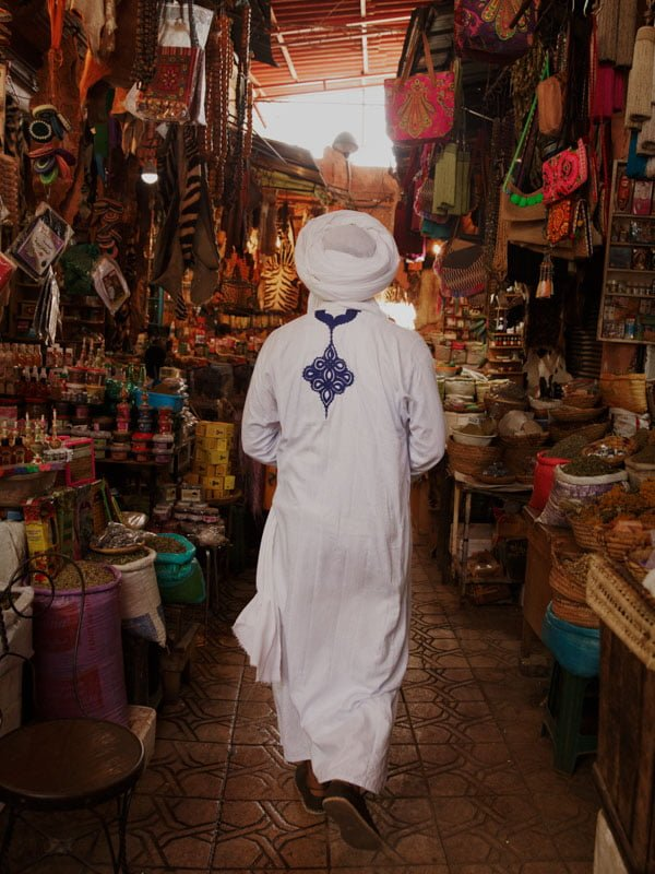 Male wearing traditional Moroccan clothing with turban walking through Marrakech market souk