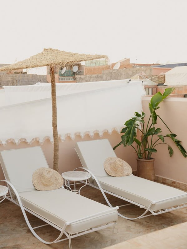 Sun Loungers and Boater Hats under Straw Parasol and Broad Leaf plant on Hotel Roof Patio