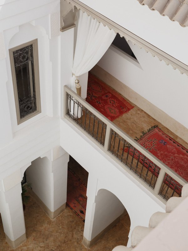 Interior balcony at Marrakech Riad LouHou hotel with red Berber Moroccan rugs