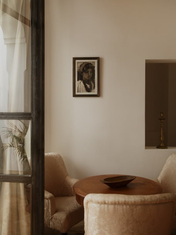 Moroccan hotel room traditional lounge chairs, table, fruit bowl, framed photograph and brass candlestick