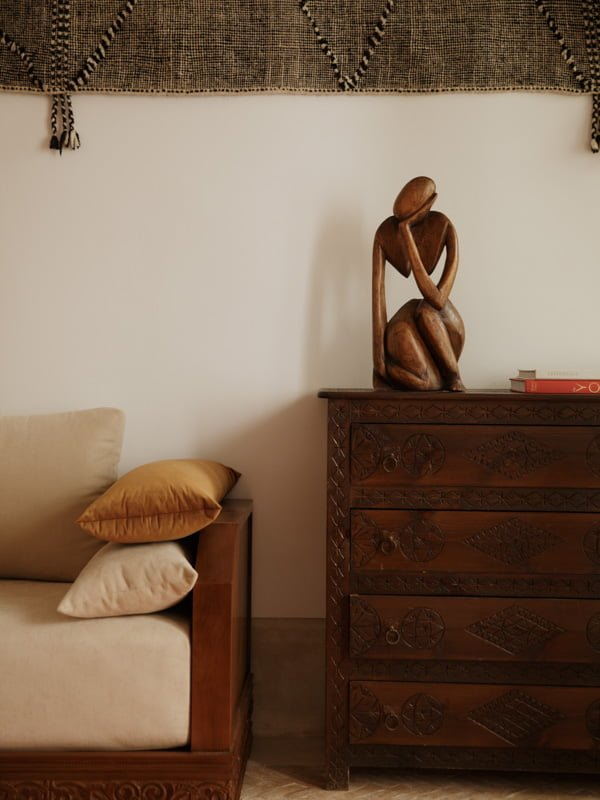 Wooden Female Sculpture on Ornate Wooden Moroccan Chest of Drawers, Couch and Wall Tapestry