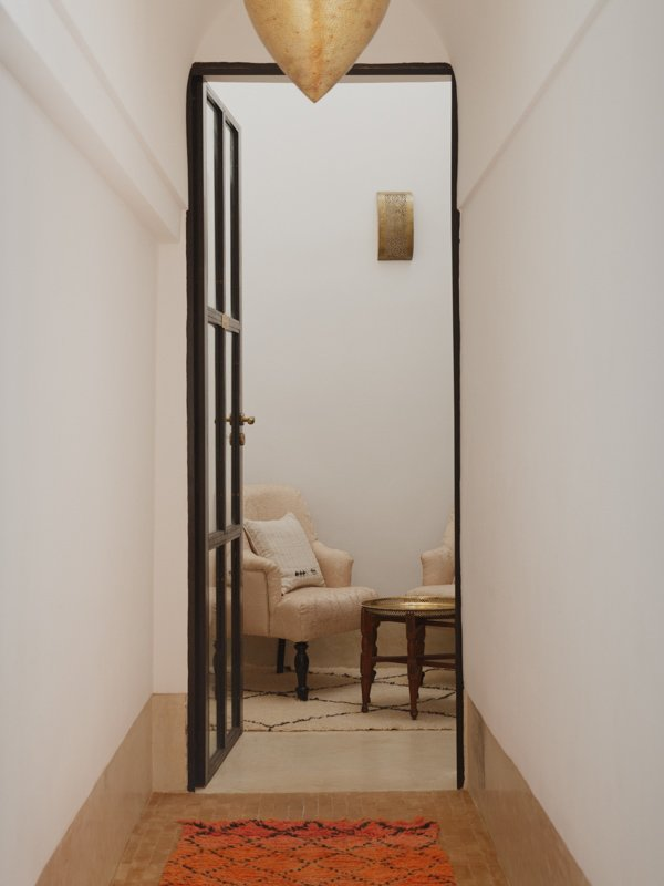 View from hallway into Riad hotel room, wooden gold topped side table with cushioned lounge chairs