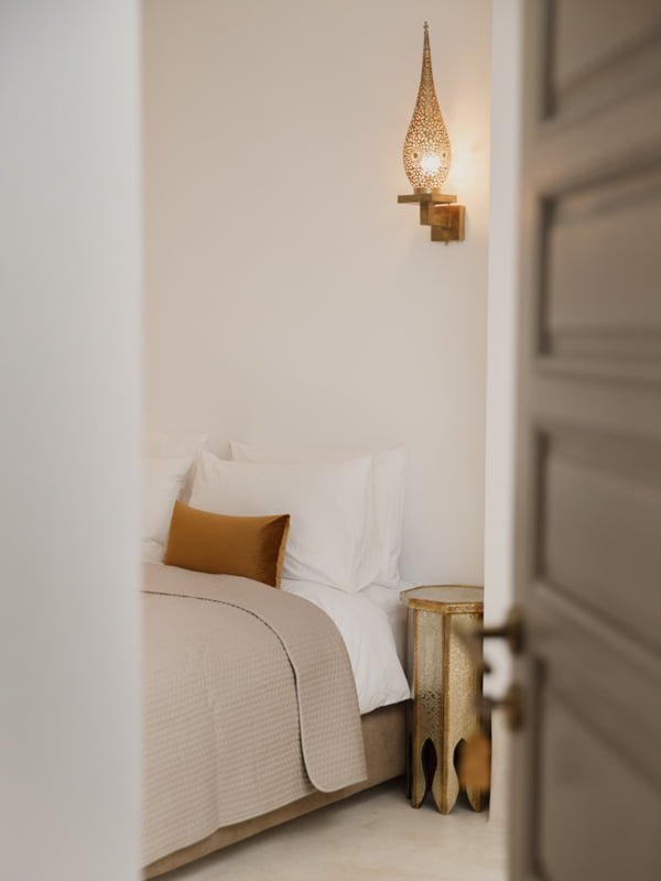 Door Open at Riad Hotel Bedroom, Double Bed, Gold Hexagonal Table, ornamental wall light