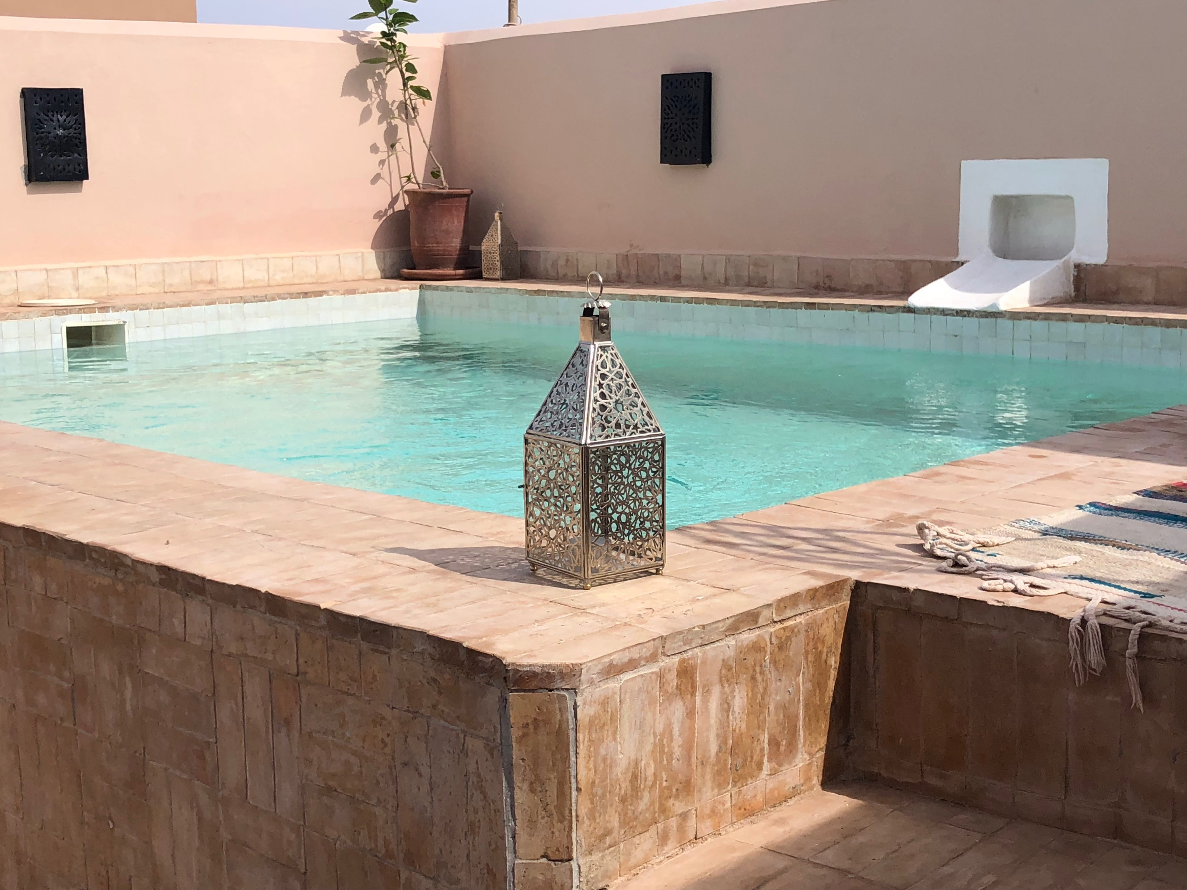Moroccan Swimming Pool Terrace with Decorative silver lanterns, Traditional Rug and Large pot plant.