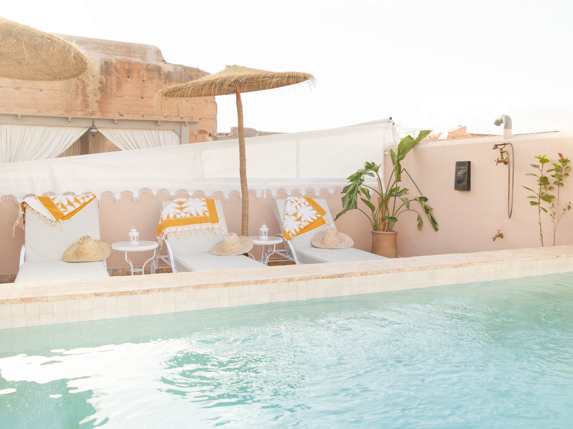 Rooftop Swimming Pool at Luxury Riad Hotel, featuring Sun loungers, Side tables, towels, sunshade, straw hats and potted broad leaf plant